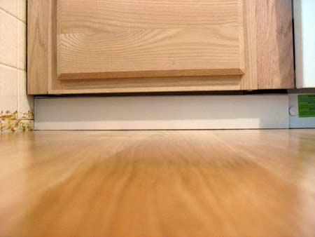 White floor base molding under base cabinets